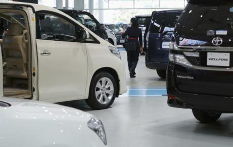 A woman walks among Toyota Motor's cars at the company's showroom in Tokyo